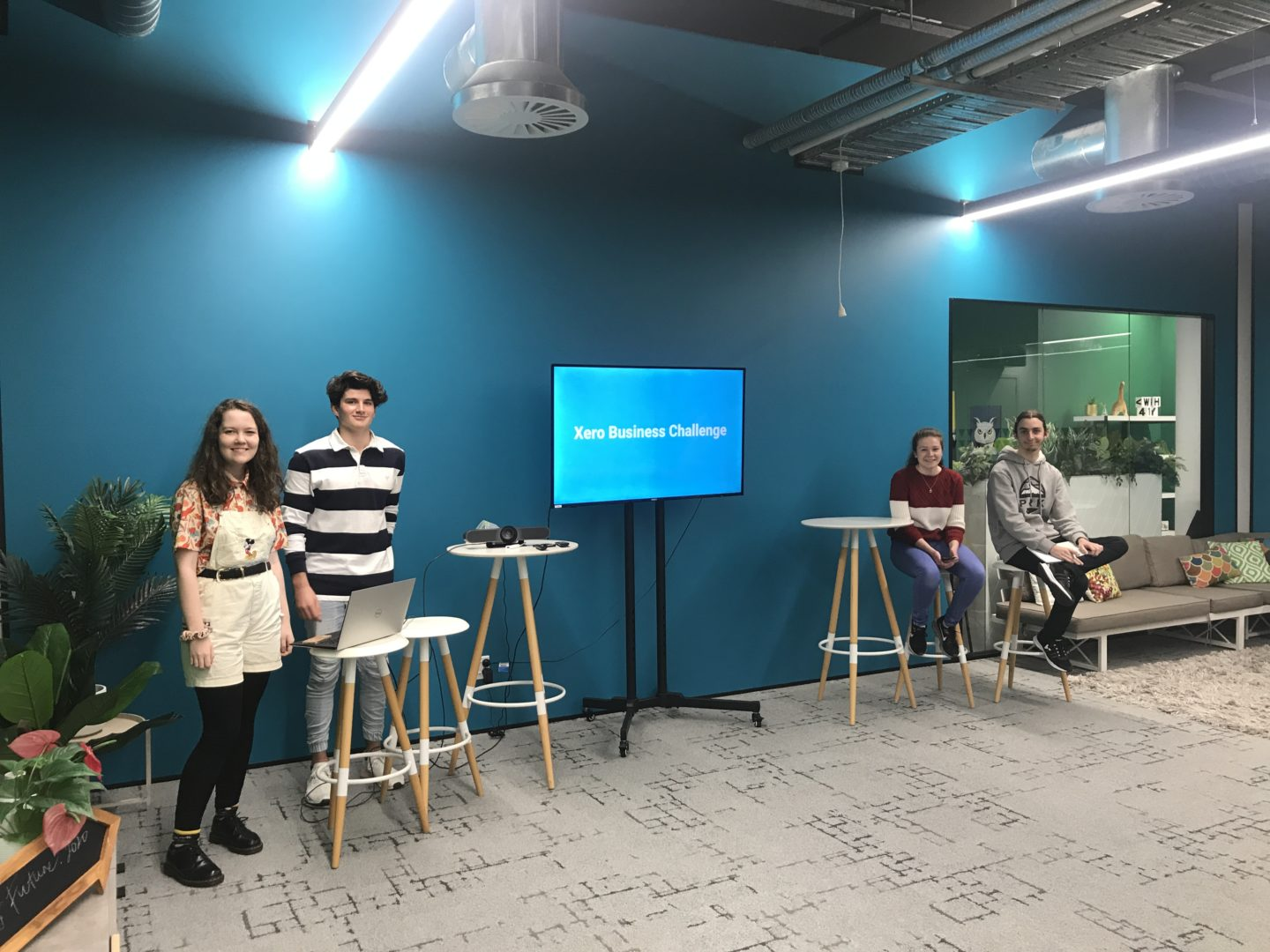 Photograph taken before the team presented on the final day. The four young people stand next to the screen and smile at the camera.